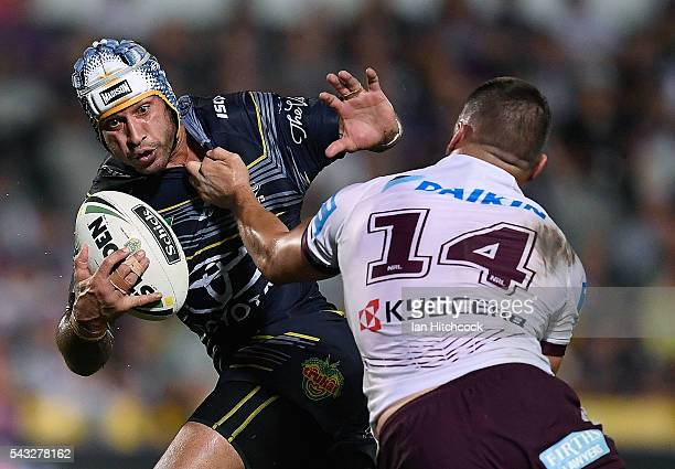 Johnathan Thurston of the Cowboys looks to fend off Lewis Brown of the Sea Eagles during the round 16 NRL match between the North Queensland Cowboys...