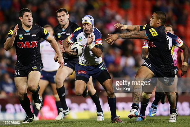 Johnathan Thurston of the Cowboys makes a break which leads to a try by Ray Thompson during the round 22 NRL match between the Penrith Panthers and...