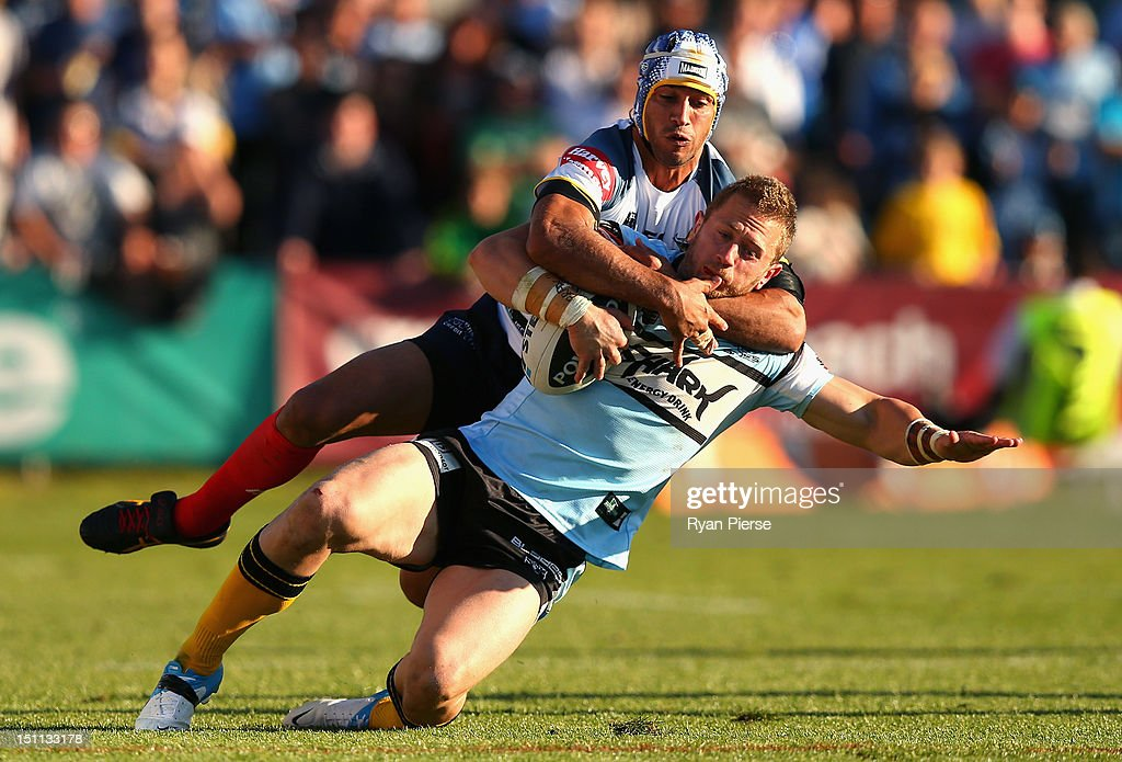 Johnathan Thurston of the Cowboys tackles Nathan Stapleton of the Sharks during the round 26 NRL match between the Crounulla Sharks and the North...