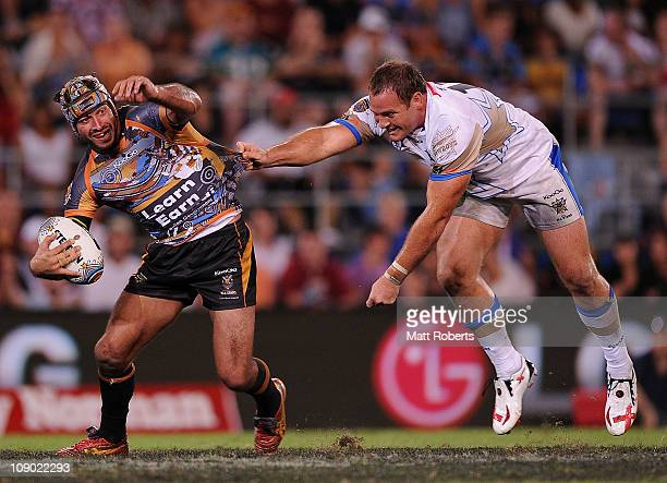 Johnathan Thurston of the Indigenous All Stars is tackled by Matthew Scott of the NRL All Stars during the match between the Indigenous All Stars and...