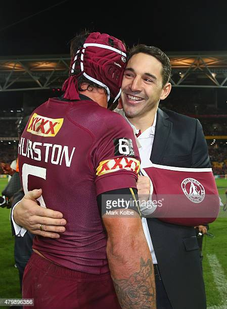 Johnathan Thurston of the Maroons and injured Maroons player Billy Slater celebrate victory during game three of the State of Origin series between...