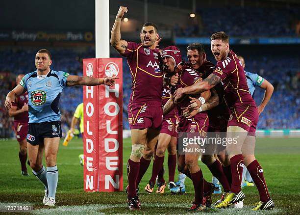 Johnathan Thurston of the Maroons celebrates with Greg Inglis after scoring the first try as Robbie Farah protests during game three of the ARL State...
