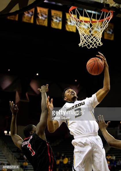 Johnathan Williams III of the Missouri Tigers grabs a rebound over Nino Johnson of the Southeast Missouri State Redhawks looks on during the game at...