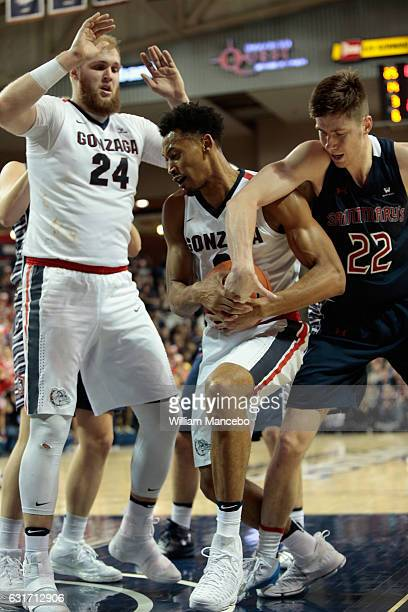 Johnathan Williams of the Gonzaga Bulldogs and Dane Pineau of the Saint Mary's Gaels battle for possession in the second half at McCarthey Athletic...
