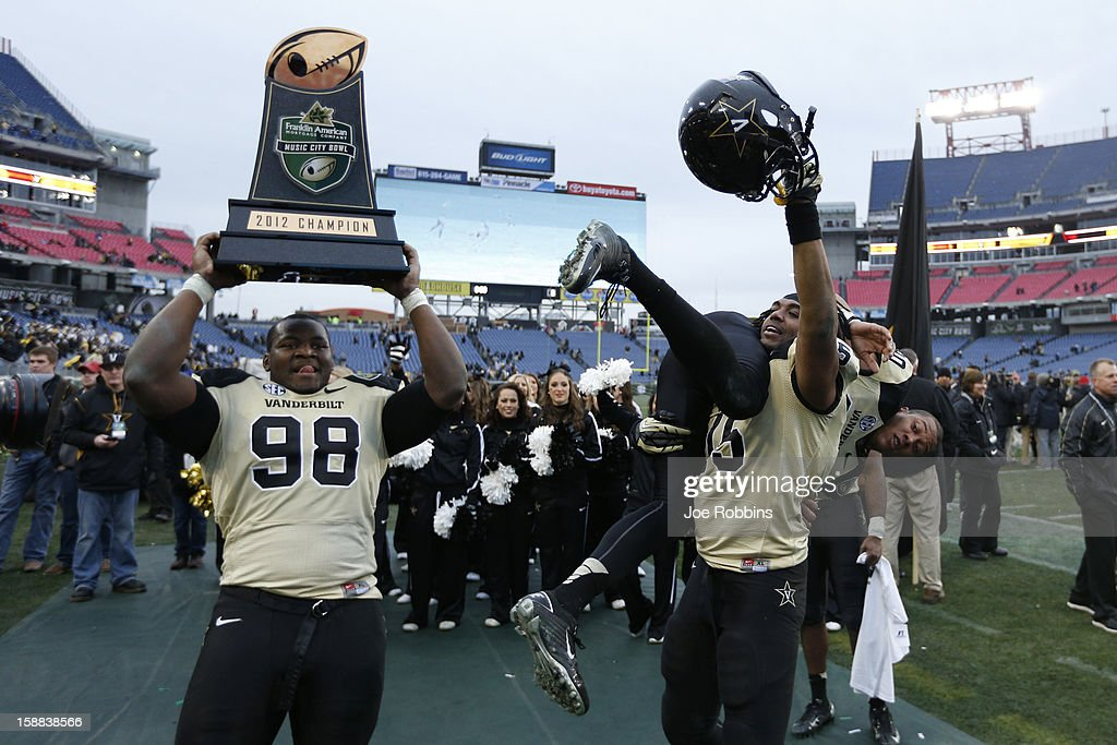Johnell Thomas #98, Archibald Barnes #15 and Chris Boyd #80 of the Vanderbilt Commodores celebrate after the game against the North Carolina State Wolfpack during the Franklin American Mortgage Music City Bowl at LP Field on December 31, 2012 in Nashville, Tennessee. Vanderbilt won 38-24.