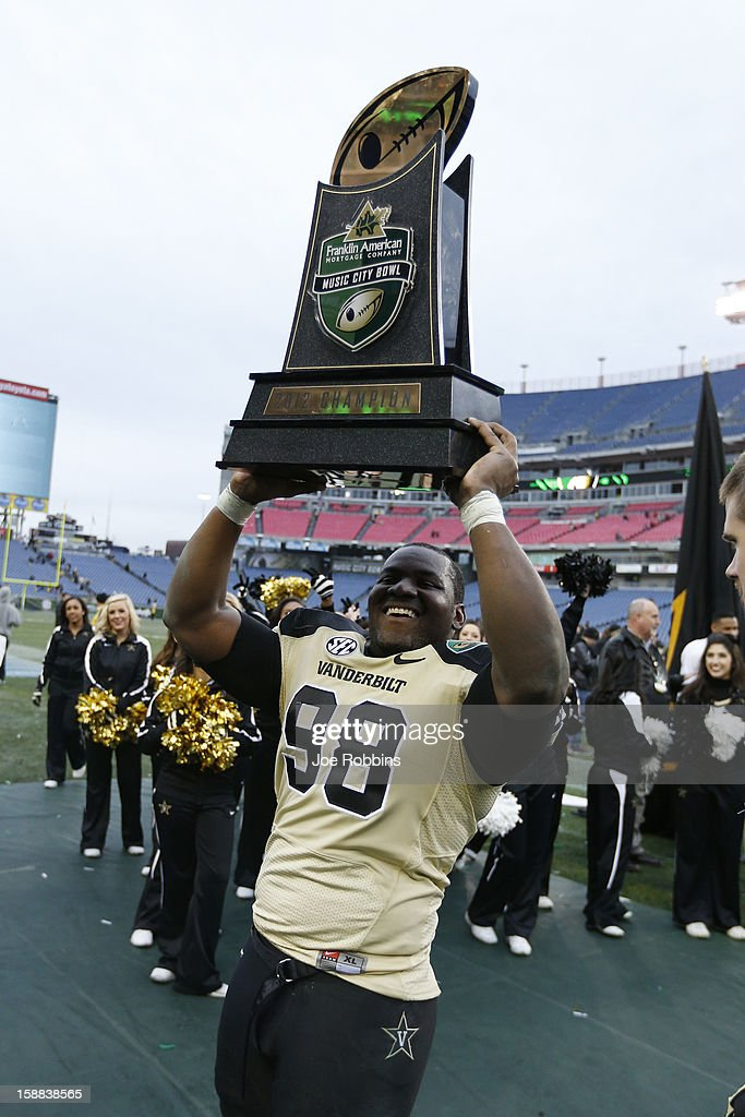 Johnell Thomas #98 of the Vanderbilt Commodores celebrates with the winning trophy after the game against the North Carolina State Wolfpack during the Franklin American Mortgage Music City Bowl at LP Field on December 31, 2012 in Nashville, Tennessee. Vanderbilt won 38-24.