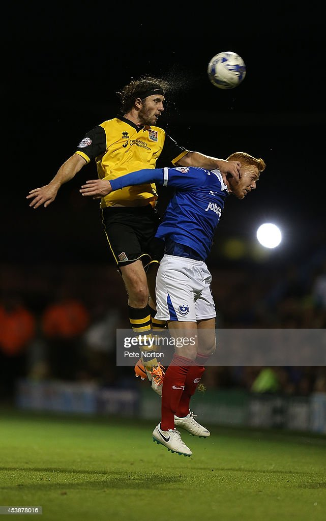 John-Joe O'Toole of Northampton Town rises above Ryan Taylor of Portsmouth to head the ball during the Sky Bet League Two match between Portsmouth and Northampton Town at Fratton Park on August 19, 2014 in Portsmouth, England.