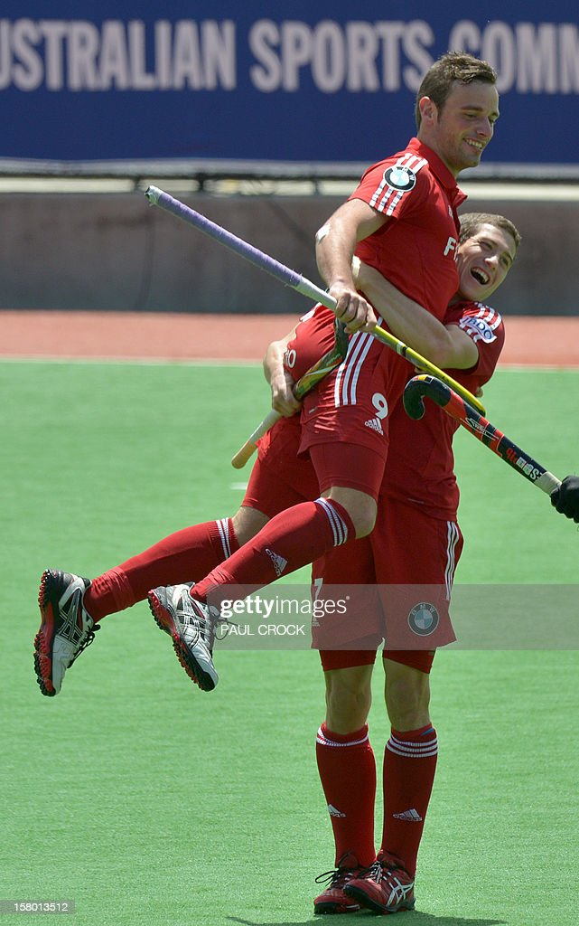 John-John Dohmen of Belgium (R) lifts team mate Sebastien Dockier (L) into the air afer he scored a goal against Germany during the match at the men's Hockey Champions Trophy tournament in Melbourne on December 9, 2012. IMAGE STRICTLY RESTRICTED TO EDITORIAL USE - STRICTLY NO COMMERCIAL USE AFP PHOTO / Paul CROCK