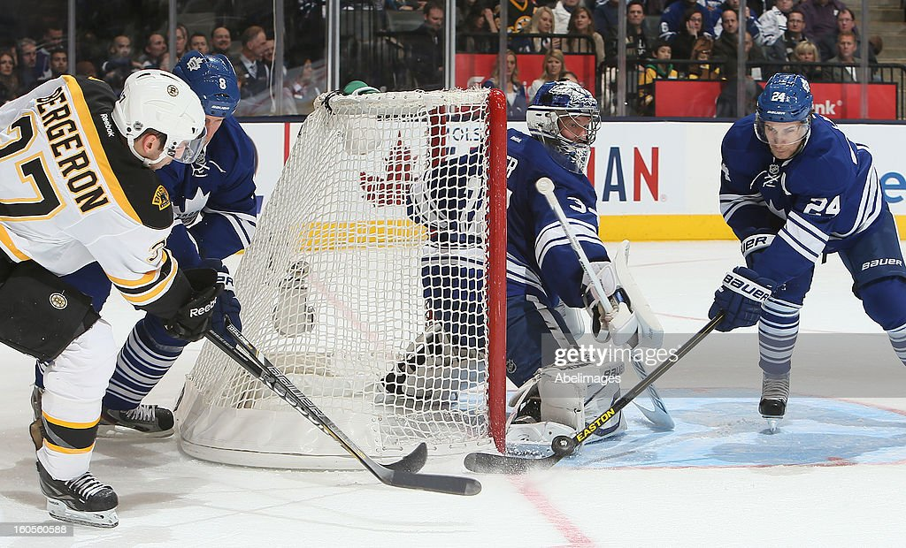John-Michael Liles #24 and James Reimer #34 of the Toronto Maple Leafs stop the wrap around on <a gi-track='captionPersonalityLinkClicked' href=/galleries/search?phrase=Patrice+Bergeron&family=editorial&specificpeople=204162 ng-click='$event.stopPropagation()'>Patrice Bergeron</a> #37 of the Boston Bruins during NHL action at the Air Canada Centre February 2, 2013 in Toronto, Ontario, Canada.