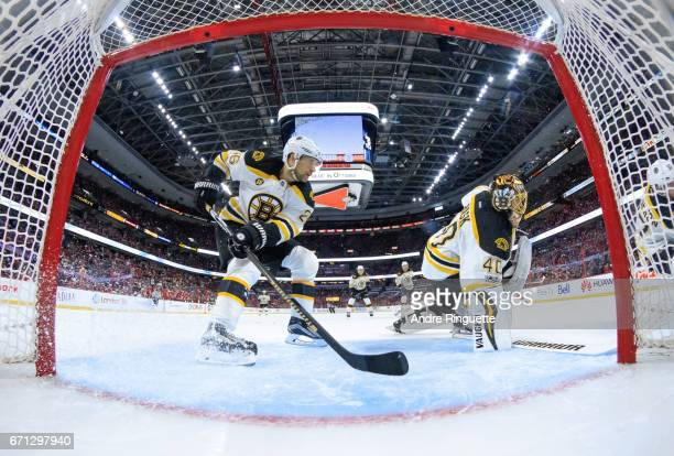 JohnMichael Liles of the Boston Bruins helps defend the net of teammate Tuukka Rask against the Ottawa Senators in Game Five of the Eastern...