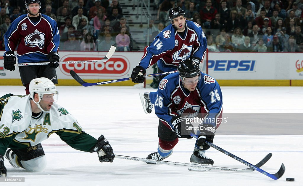 JohnMichael Liles of the Colorado Avalanche takes the puck away from Bill Guerin of the Dallas Stars during Game 3 of the Western Conference...