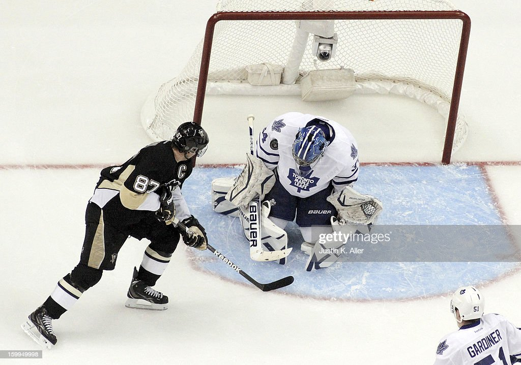 John-Michael Liles #24 of the Toronto Maple Leafs makes a save on Sidney Crosby #87 of the Pittsburgh Penguins during the game at Consol Energy Center on January 23, 2013 in Pittsburgh, Pennsylvania. The Leafs defeated the Pens 5-2.