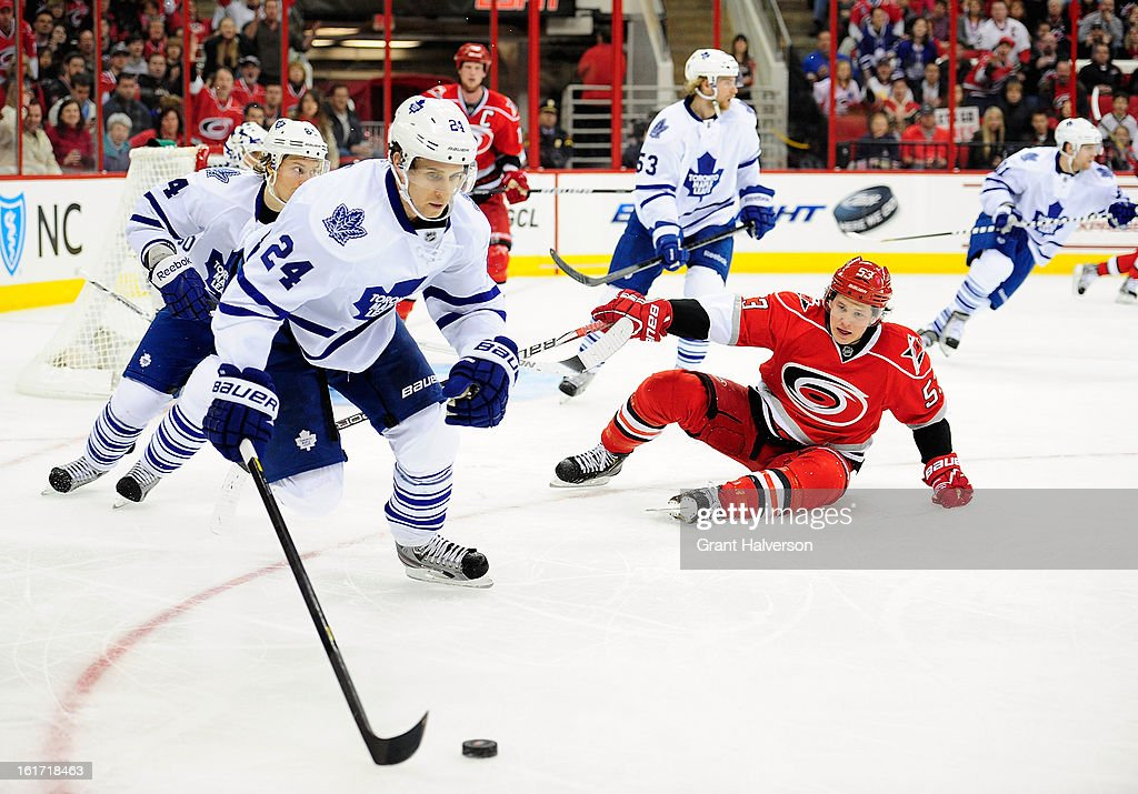 John-Michael Liles #24 of the Toronto Maple Leafs moves the puck up the ice as Jeff Skinner #53 of the Carolina Hurricanes looks on during play at PNC Arena on February 14, 2013 in Raleigh, North Carolina.