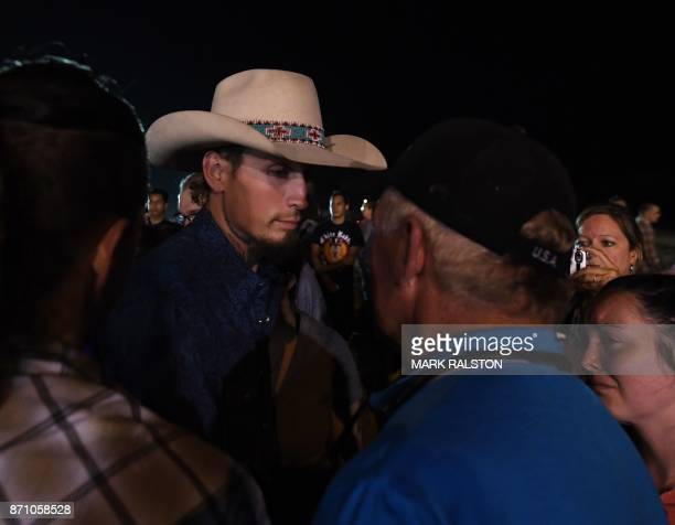 Johnnie Langendorff one of the two men who chased after suspected killer Devin Kelley speaks with a man during a vigil in Sutherland Springs Texas on...