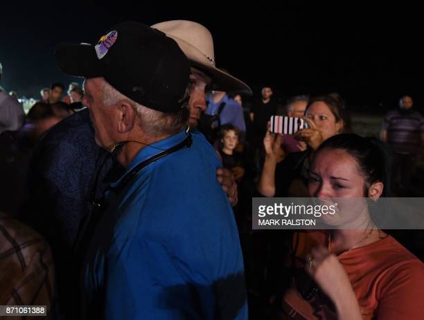 Johnnie Langendorff one of the two men who chased after suspected killer Devin Kelley embraces a man during a vigil in Sutherland Springs Texas on...