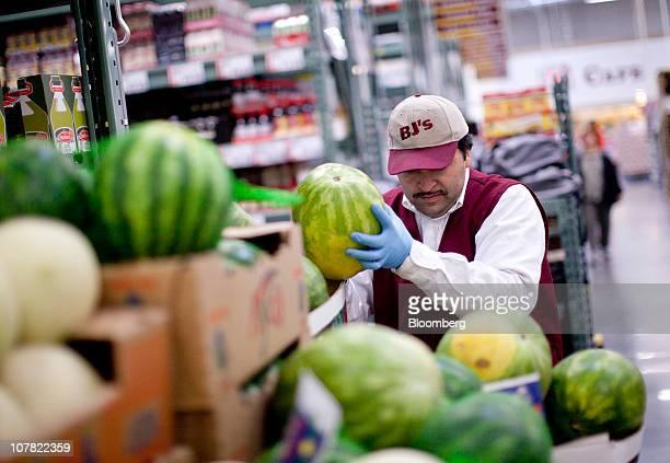 Johnny Alvarez arranges watermelons inside a BJ's Wholesale Club store in Falls Church Virginia US on Thursday Dec 30 2010 BJ's Wholesale Club Inc...