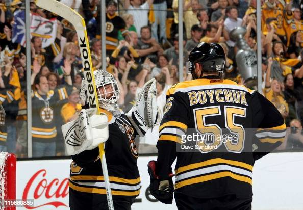 Johnny Boychuk and goaltender Tim Thomas of the Boston Bruins celebrate their 40 victory over the Vancouver Canucks in Game Four of the 2011 NHL...