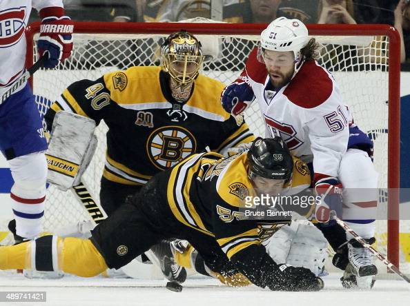 Johnny Boychuk of the Boston Bruins battles with David Desharnais of the Montreal Canadiens during Game Five of the Second Round of the 2014 NHL...