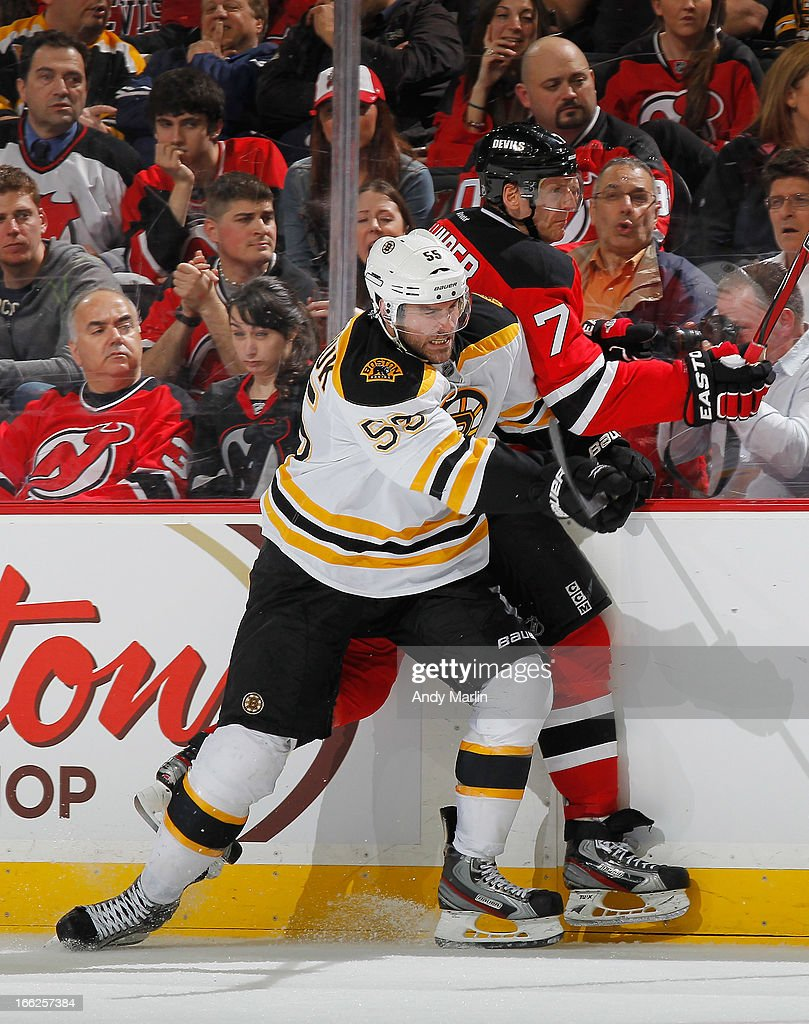 <a gi-track='captionPersonalityLinkClicked' href=/galleries/search?phrase=Johnny+Boychuk&family=editorial&specificpeople=2125695 ng-click='$event.stopPropagation()'>Johnny Boychuk</a> #55 of the Boston Bruins checks <a gi-track='captionPersonalityLinkClicked' href=/galleries/search?phrase=Henrik+Tallinder&family=editorial&specificpeople=204661 ng-click='$event.stopPropagation()'>Henrik Tallinder</a> #7 of the New Jersey Devils during the game at the Prudential Center on April 10, 2013 in Newark, New Jersey.