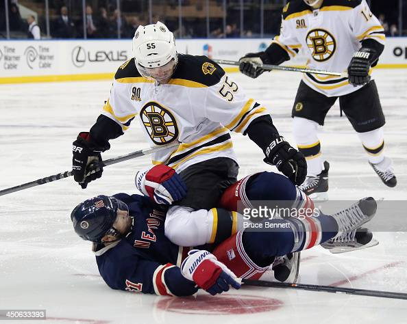 Johnny Boychuk of the Boston Bruins checks Rick Nash of the New York Rangers during the second period at Madison Square Garden on November 19 2013 in...