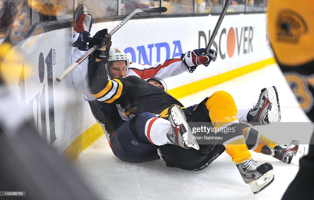 Johnny Boychuk #55 of the Boston Bruins collides Matt Hendricks #26 of the Washington Capitals in Game Five of the Eastern Conference Quarterfinals during the 2012 NHL Stanley Cup Playoffs at TD Garden on April 21, 2012 in Boston, Massachusetts.
