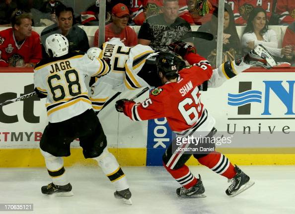 Johnny Boychuk of the Boston Bruins flys through the air against the Chicago Blackhawks in Game Two of the NHL 2013 Stanley Cup Final at United...