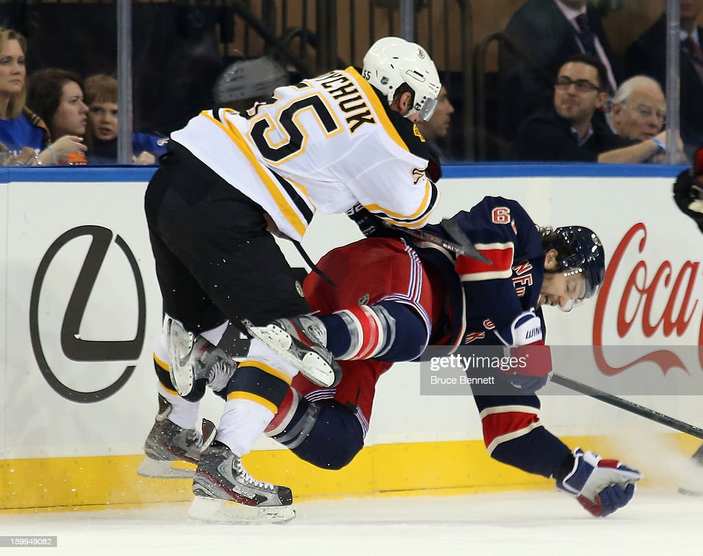 Johnny Boychuk #55 of the Boston Bruins hits Carl Hagelin #62 of the New York Rangers at Madison Square Garden on January 23, 2013 in New York City.