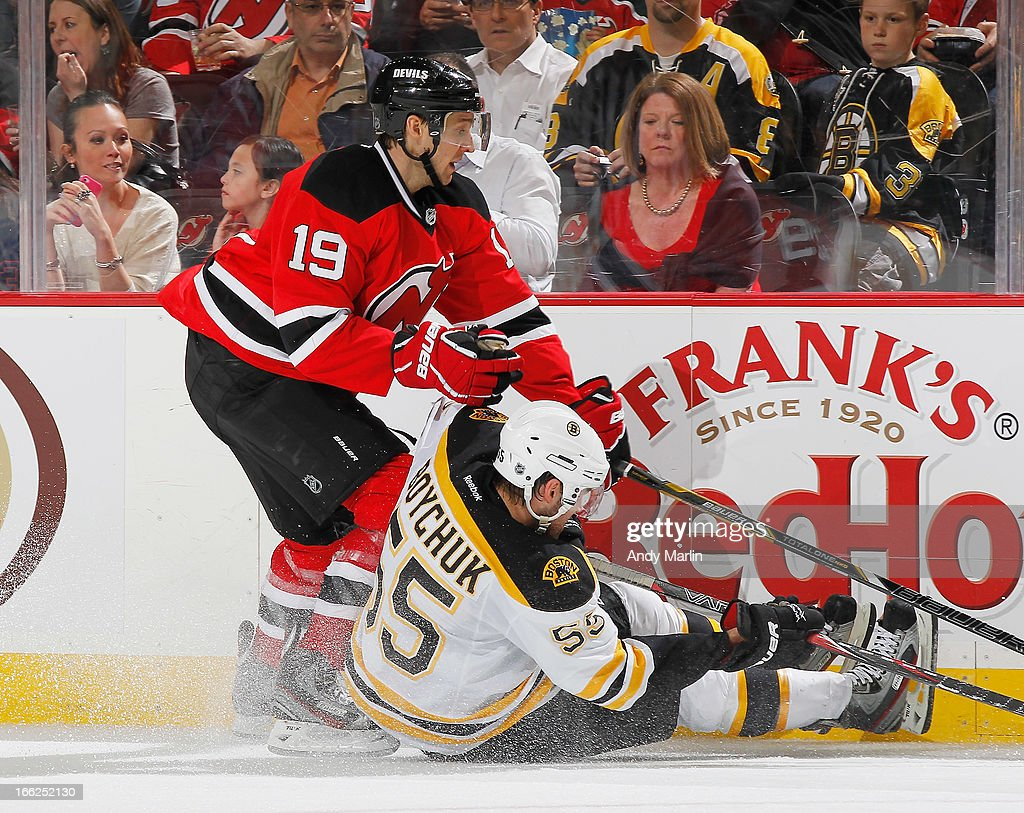 <a gi-track='captionPersonalityLinkClicked' href=/galleries/search?phrase=Johnny+Boychuk&family=editorial&specificpeople=2125695 ng-click='$event.stopPropagation()'>Johnny Boychuk</a> #53 of the Boston Bruins is knocked to the ice by <a gi-track='captionPersonalityLinkClicked' href=/galleries/search?phrase=Travis+Zajac&family=editorial&specificpeople=864182 ng-click='$event.stopPropagation()'>Travis Zajac</a> #19 of the New Jersey Devils during the game at the Prudential Center on April 10, 2013 in Newark, New Jersey.