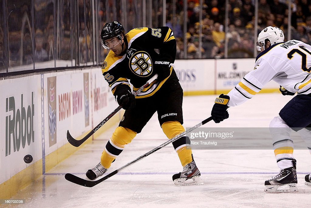 Johnny Boychuk #55 of the Boston Bruins sends the puck into the zone as Thomas Vanek #26 of the Buffalo Sabres defends during a game at the TD Garden on January 31, 2013 in Boston, Massachusetts.