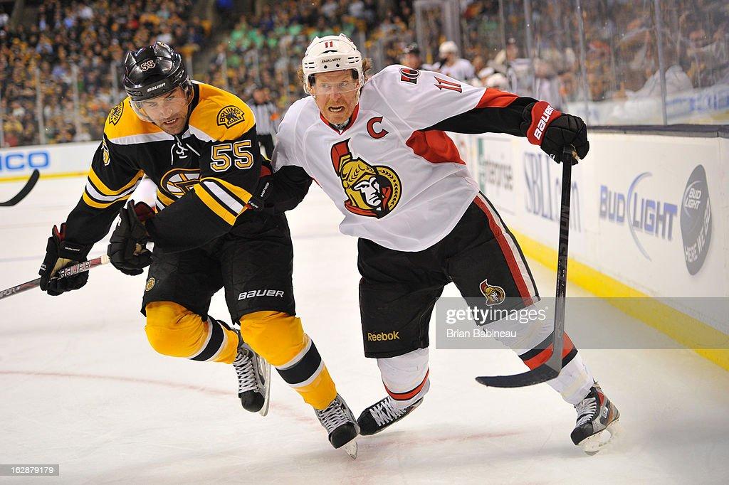 Johnny Boychuk #55 of the Boston Bruins skates hard against Daniel Alfredsson #11 of the Ottawa Senators at the TD Garden on February 28, 2013 in Boston, Massachusetts.