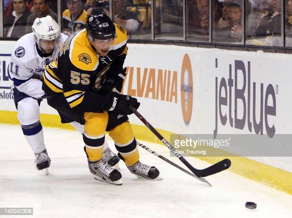 Johnny Boychuk of the Boston Bruins skates with the puck against Tom Pyatt of the Tampa Bay Lightning at TD Garden on March 27 2012 in Boston...