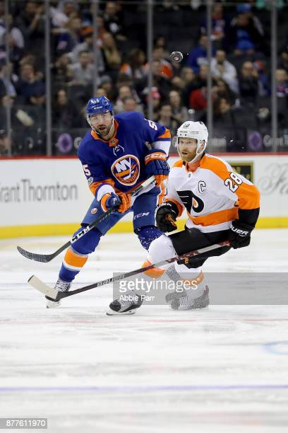 Johnny Boychuk of the New York Islanders and Claude Giroux of the Philadelphia Flyers chase after the puck in the second period during their game at...