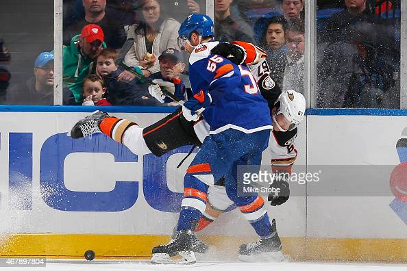Johnny Boychuk of the New York Islanders and Rickard Rakell of the Anaheim Ducks battle for the puck along the boards at Nassau Veterans Memorial...