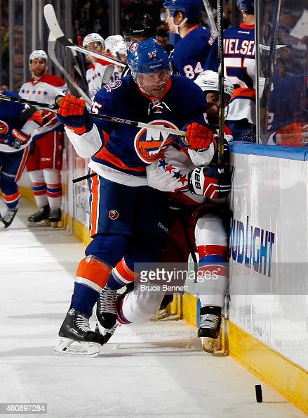 Johnny Boychuk of the New York Islanders checks Brooks Laich of the Washington Capitals during a game at the Nassau Veterans Memorial Coliseum on...