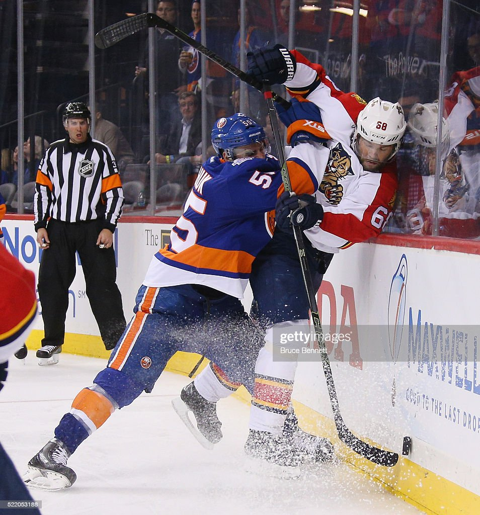 Johnny Boychuk of the New York Islanders checks Jaromir Jagr of the Florida Panthers into the boards during the third period during Game Three of the...