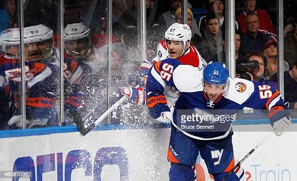 Johnny Boychuk of the New York Islanders hits Max Pacioretty of the Montreal Canadiens in the third period at Nassau Veterans Memorial Coliseum on...
