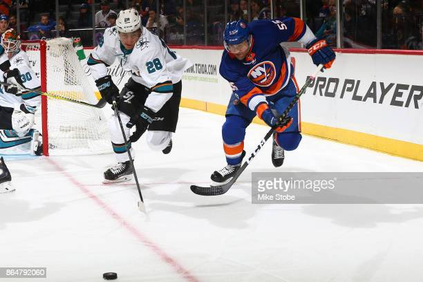 Johnny Boychuk of the New York Islanders races for the puck with Timo Meier of the San Jose Sharks at Barclays Center on October 21 2017 in New York...