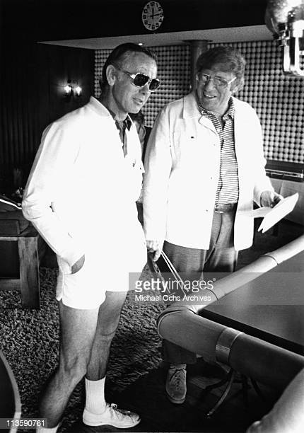 Johnny Carson host of the Tonight Show chats with a fellow member at a private Tennis club circa 1975 in Los Angeles California