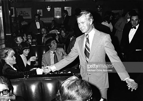 Johnny Carson host of the Tonight Show greets gossip columnist Rona Barrett at a restaurant circa 1973 in Los Angeles California
