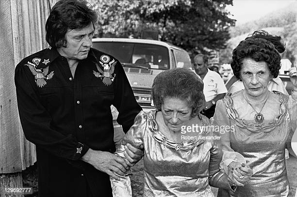Johnny Cash walks with Maybelle Carter center and Sara Carter at the AP Carter Memorial Festival in Maces Springs Virginia AP Carter was the leader...