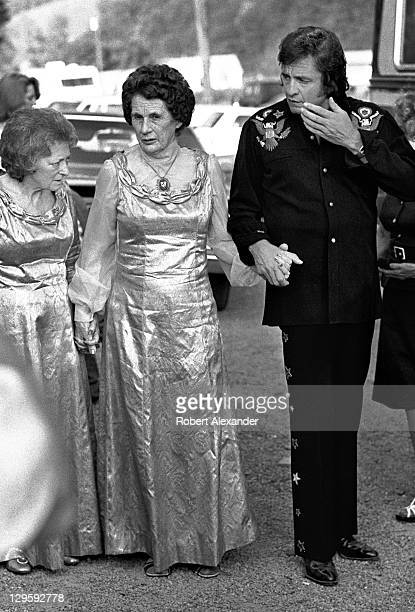 Johnny Cash walks with Maybelle Carter far left and Sara Carter at the AP Carter Memorial Festival in Maces Springs Virginia AP Carter was the leader...