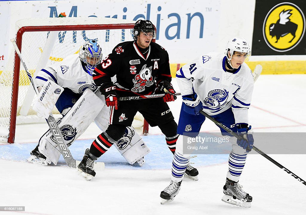 Johnny Corneil #23 of the Niagara IceDogs gets in front of goalie Jacob Ingham #1 of the Mississauga Steelheads as Nicolas Hague #41 of the ice dogs helps defend during game action on October 21, 2016 at Hershey Centre in Mississauga, Ontario, Canada.