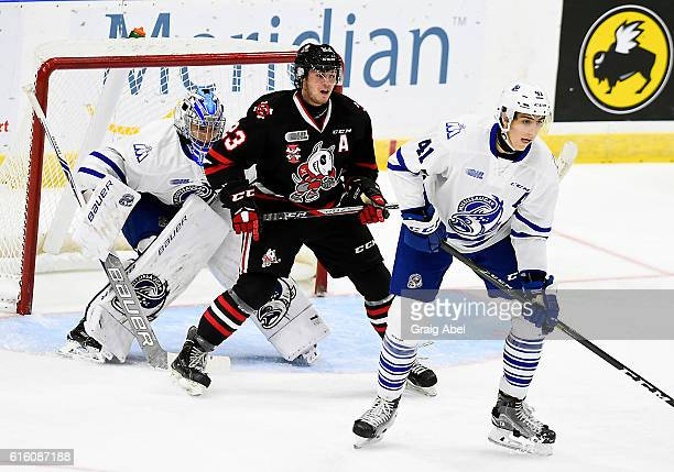 Johnny Corneil of the Niagara IceDogs gets in front of goalie Jacob Ingham of the Mississauga Steelheads as Nicolas Hague of the ice dogs helps...