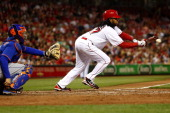Johnny Cueto of the Cincinnati Reds lays down a bunt against the New York Mets at Great American Ball Park on September 23 2013 in Cincinnati Ohio...