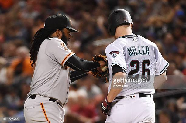 Johnny Cueto of the San Francisco Giants tags out Shelby Miller of the Arizona Diamondbacks during the fifth inning at Chase Field on July 1 2016 in...