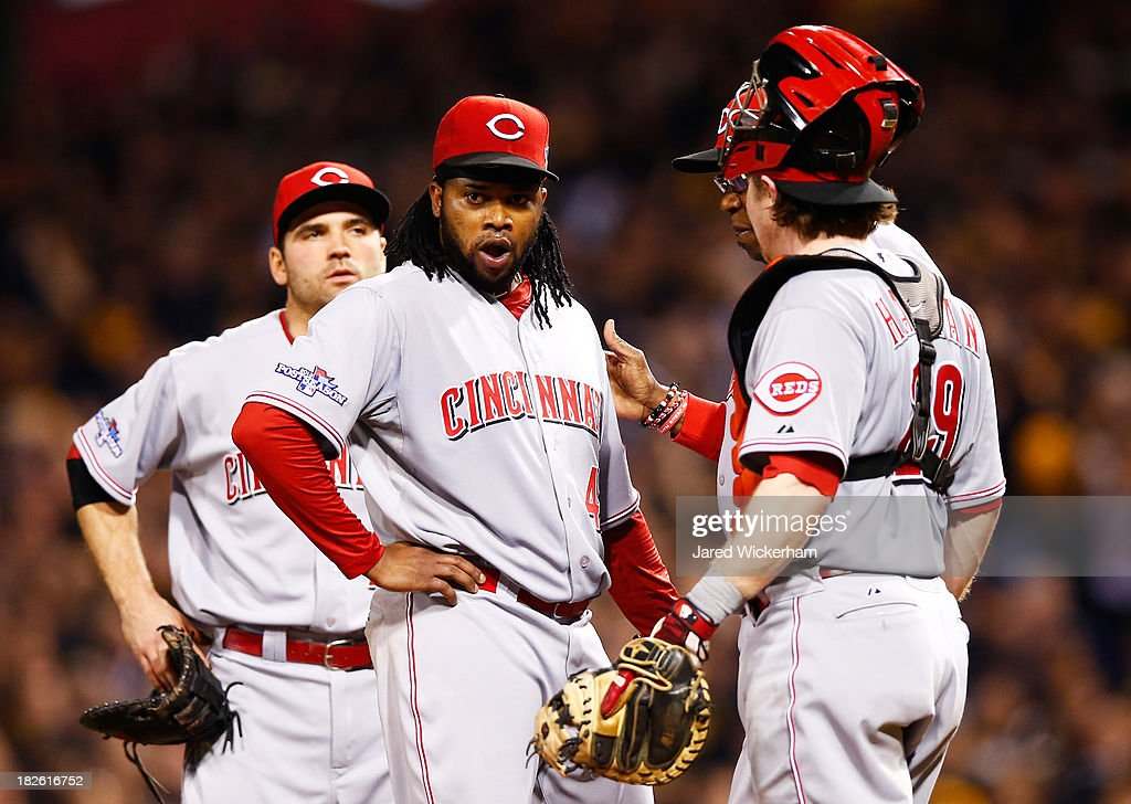 Johnny Cueto #47 talks to Ryan Hanigan #29 and Manager Dusty Baker #12 of the Cincinnati Reds in the third inning against the Pittsburgh Pirates during the National League Wild Card game at PNC Park on October 1, 2013 in Pittsburgh, Pennsylvania.