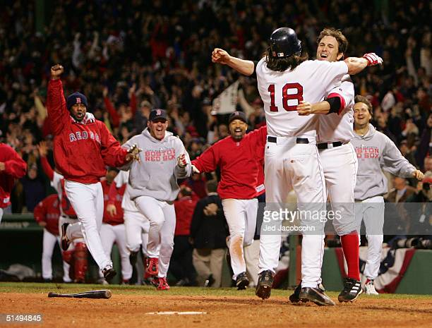 Johnny Damon of the Boston Red Sox celebrates with teammate Doug Mientkiewicz and the rest of the Red Sox team after scoring the game winning run on...