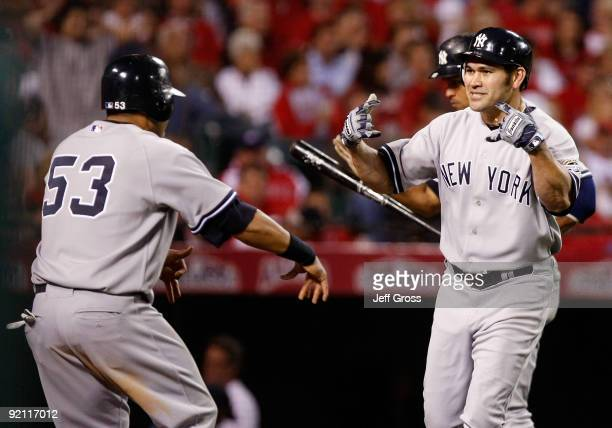 Johnny Damon of the New York Yankees celebrates with teammate Melky Cabrera after Damon hit a two run home run during the eighth inning in Game Four...