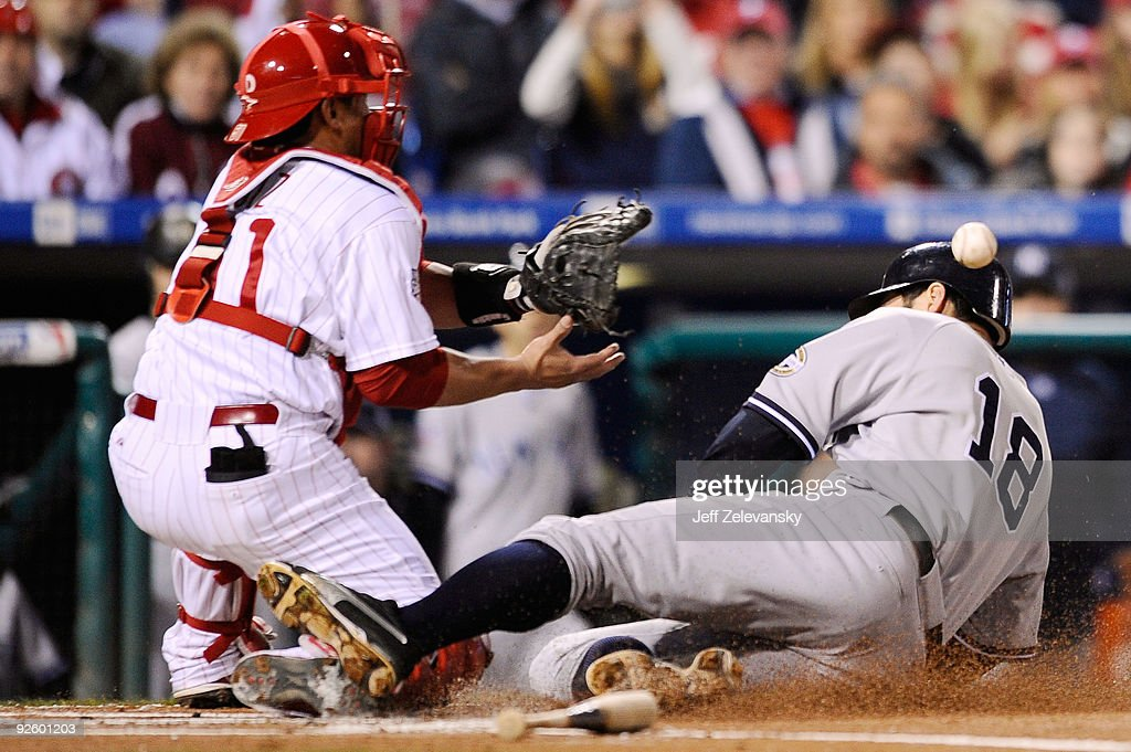 Johnny Damon of the New York Yankees slides safely into home on a sacrifice fly by Jorge Posada ahead of the throw to Carlos Ruiz of the Philadelphia...
