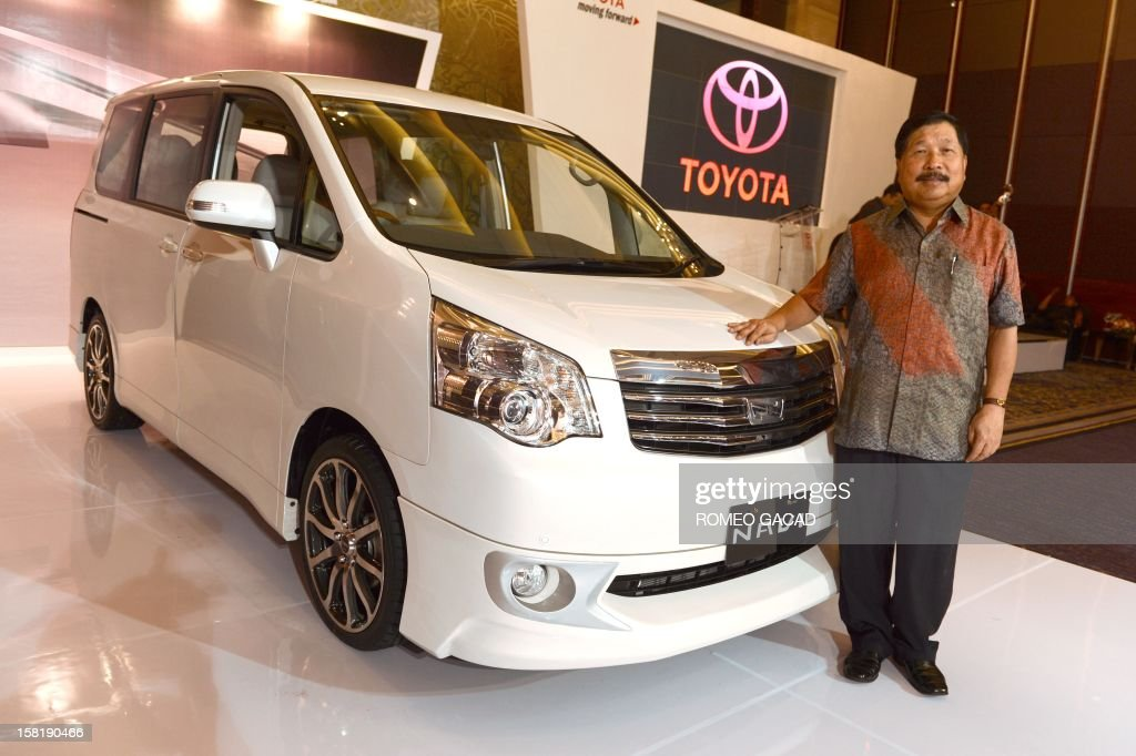 Johnny Darmawan, President Director Toyota Astra Motor poses beside the 2013 model of Toyota Nav1 during official launch in Jakarta on December 11, 2012. Nav1, the new six-seater multi-purpose vehicle (MPV) car model of Toyota was launched as officials of Indonesian automotive industry predict domestic car sales to reach between 1.08 million and 1.1 million units next year in 2013.